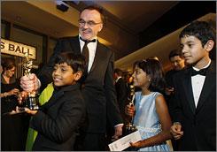 Slumdog Millionaire  director Danny Boyle shares the spoils of victory with his child actors  Azharuddin Mohammed Ismail, left, Rubina Ali and Ayush Mahesh Khedekar.