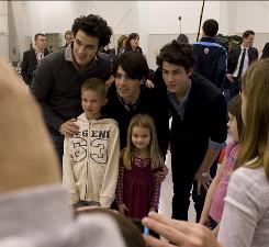 Even better than in 3-D? In the flesh: Kevin, left, Joe and Nick Jonas get a picture with Jared, 8, and Ella Papke, 4, after a news conference at Wilson Air Center in Charlotte. Then, the JoBros headed off to surprise fans seeing their movie Saturday at a local theater.