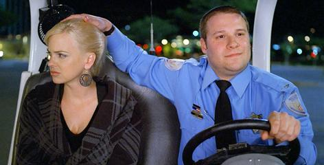 Mall security guard Ronnie (Seth Rogen) patrols the area looking for scofflaws, and one notorious flasher, in Observe and Report. Anna Faris plays Brandi, the floozy of Ronnie's dreams.