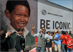 Usher, center, shows off his new billboard while his mother, Jonnetta Patton, left, and local children look on.