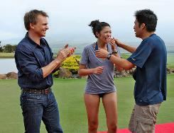Amazing Race host Phil Keoghan, left, congratulates the brother-and-sister team ofTammy Jih and Victor Jih at the finish line in Hawaii after they won the competition.