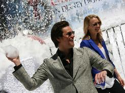 """Jim Carrey and Robin Wright Penn play with the """"snow"""" (biodegradable bubbles) Monday in Cannes, France, as the film festival got a peek at Disney's 3-D A Christmas Carol."""