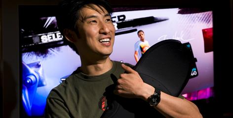 Josh Tsui of Robomodo holds the skateboard-shaped controller his company helped design for the Tony Hawk: Ride game due later this year. The controller uses motion and light sensors.