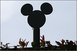 A silhouette of Mickey Mouse tops fencing at the Walt Disney Co. compound in Burbank, Calif.