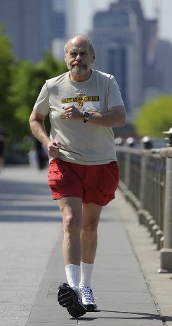 Crime novelist Lawrence Block demonstrates his racewalking gait next to the Hudson River in New York City.