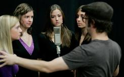Hannah Jones, left, Lily Roberts, Haley Chaney and Kaitlyn Slight of the a cappella group Lorelis take direction from Ben Folds, right.