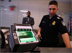 When international passengers enter the United States, they are fingerprinted. Here, a security officer is seen with a fingerprinting machine at JFK International Airport in New York in March 2008.