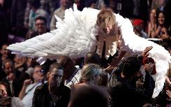 Winging it: Eminem, left, stormed out of the auditorium after Sacha Baron Cohen landed on him.
