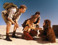 In a world of fantastic creatures: Rick (Will Ferrell, left), Holly (Anna Friel) and Will (Danny McBride) land in an alternate universe, where they meet a primate named Chaka (Jorma Taccone).
