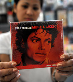 A woman holds up the last copy of a Michael Jackson greatest-hits compliation CD at a record store in Manila. Sales of Jackson books, CDs, DVDs and downloads have skyrocketed around the world since his sudden death Thursday.