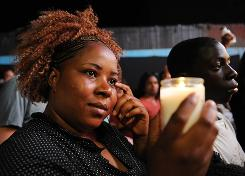A woman with a candle was part of the crowd in front of Harlem's Apollo Theater on Thursday to honor the life of Michael Jackson.