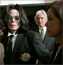 Michael Jackson leaves court with defense attorney Thomas Mesereau Jr. on June 13, 2005, following his acquittal on child molestation charges.