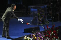 Jermaine Jackson, wearing one white sequined glove, tosses the rose from his lapel while performing at the Michael Jackson public memorial service at L.A.'s Staples Center.