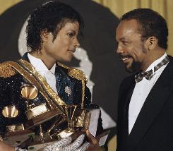 Michael Jackson holds his eight awards as he chats with Quincy Jones at the Grammy Awards in Los Angeles in 1984. Twenty-five years later, questions are swirling about unreleased music from the superstar, who died June 25 at age 50.