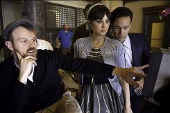 Director Marc Webb, left, Zooey Deschanel and Joseph Gordon-Levitt watch a playback of a scene from the music video.
