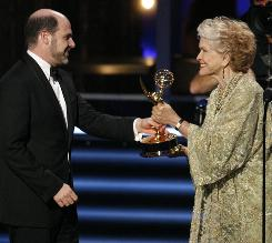 Mad Men creater Matthew Weiner accepts the award for outstanding writing for a drama series from Ellen Burstyn at Sunday's Emmy Awards.