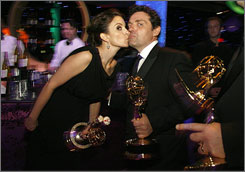 30 Rock creator Tina Fey kisses her husband, Jeff Richmond, while he helps hold her loot at the Goevernors Ball after the Emmy Awards. Her show  the most nominated this year  picked up awards for best comedy and best comedic actor, among others.