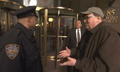 Storming the gates: Filmmaker Michael Moore talks to a police officer outside Goldman Sachs headquarters in New York City in Capitalism: A Love Story.