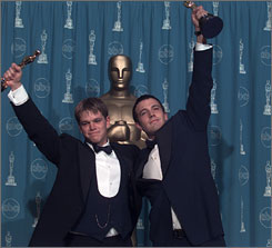Pals Matt Damon, left, and Ben Affleck celebrate after taking home the Oscar for Best Original Screenplay in 1998 for their film, Good Will Hunting. The New England Genealogical Society recently discovered that the childhood friends are also distant cousins.
