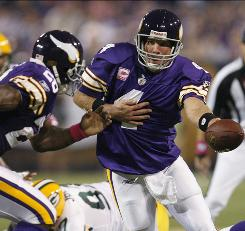 See how they run: Vikings QB Brett Favre hands off to Adrian Peterson in 30-23 win.