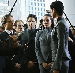 Alien leader Anna (Morena Baccarin, right) takes a liking to a newsman (Scott Wolf, left).
