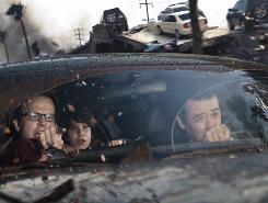 Doomsday drive: Thomas McCarthy, left, Liam James and John Cusack try to outrun catastrophe in 2012, out Friday. The film joins cable TV and Internet speculation about the apocalypse based on the Mayan calendar.