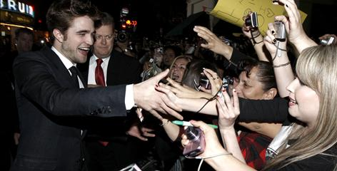 Meet and greet: Robert Pattinson, with bodyguards in tow, takes time to shake the hands of fans, some of whom had camped out for days before the premiere.
