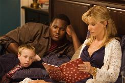 Leigh Anne Tuohy (Sandra Bullock) reads to son S.J. (Jae Head) and Michael Oher (Quinton Aaron) in The Blind Side, which is based on a true story.