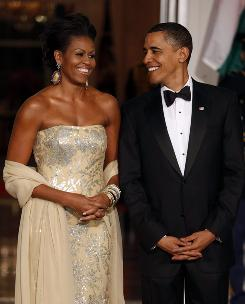 President Obama and first lady Michelle Obama await the arrival of India's Prime Minister Manmohan Singh and his wife Gursharan Kaur for a state dinner at the White House on Tuesday. The first lady sported a dress by Indian-born American designer Naeem Khan.
