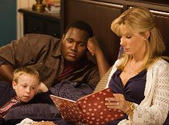Blitzed: Jae Head, left, Quinton Aaron and Sandra Bullock in The Blind Side, which took in $20.4 million this weekend.