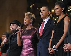 Sugarland's Kristian Bush, left, and Mary J. Blige join the Obamas in song Sunday at the National Building Museum.