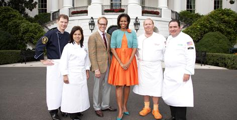 At the White House, Iron Chef host Alton Brown and first lady Michelle Obama divide the competitors: Bobby Flay and White House executive chef Cristeta Comerford, at left, vs. Mario Batali and Emeril Lagasse.