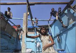 Rubina Ali, child star of Oscar-winning movie Slumdog Millionaire , stands near her damaged shack after civic authorities demolished that in Mumbai, India.