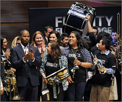 Oscar-winning actor Jamie Foxx, left, claps as students try out their newly donated instruments at Disney Hall in Los Angeles during the Fidelity FutureStage event.