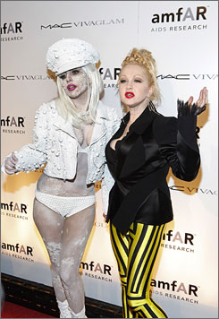 Lady Gaga, left, with a pearl-studded face, makes quite an entrance with pop queen Cyndi Lauper at the amfAR New York Gala.