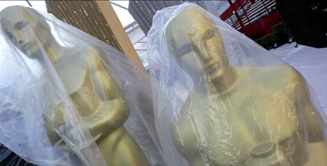 Oscar statues wrapped in plastic wait along the red carpet Thursday outside the Kodak Theatre in preparation for Sunday night's 82nd Academy Awards.