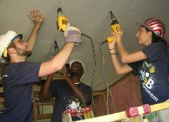Florida International University students Joseph Barrios, left, Mark Rosen and Lilia Storey work on the interior of a Habitat for Humanity house in Phoenix over spring break last year.