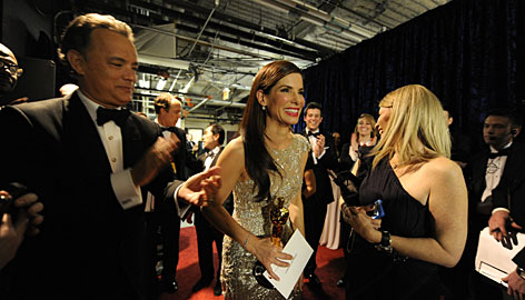 Presenter Tom Hanks applauds first-time winner Sandra Bullock.