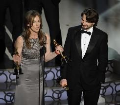 The Hurt Locker director Kathryn Bigelow and writer Mark Boal accept the best-picture trophy.
