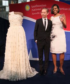First lady Michelle Obama and inaugural dress designer Jason Wu look at the inaugural gown she wore to the inaugural balls and is now on display at the Smithsonian Museum of American History.