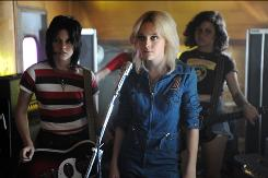 Joan Jett (Kristen Stewart, left), Cherie Currie (Dakota Fanning) and Robin (Alia Shawkat) are a teen band rising to rock stardom in The Runaways.