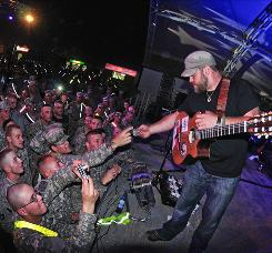 Zac Brown accepts patches from soldiers to glue on his guitar after his band's Wednesday performance at Camp Buehring in Kuwait.