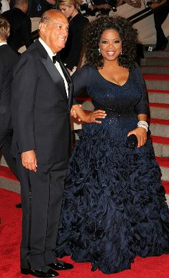 Daytime TV host and event co-chair Oprah Winfrey walks the red carpet with Oscar de la Renta, who designed her dress. She said fashion fundraiser was &quot;a dream come true for me.&quot;