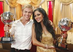 Dancing With the Stars champs Nicole Scherzinger and Derek Hough hoist their hardware.