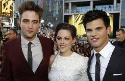 Robert Pattinson, Kristen Stewart and Taylor Lautner take a break from the fans to pose for a photo at the Eclipse premiere.