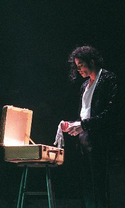 Germany, 1997: Michael Jackson delves into a suitcase for one of his signature items  a sequined glove  during a concert.