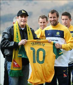 John Travolta, left, shows off his Australian team jersey presented to him by the team's captain Lucas Neill during a press conference outside the team's hotel in Muldersdrift, South Africa on June 11.