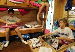 All bunked up: Hallie Cain, left, of McLean, Va., writes a birthday letter home to her mother while Ariana Aulisi packs up her belongings at Camp Netimus.