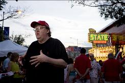 Director Michael Moore stands on Front Street in Traverse City, Mich., during the Traverse City Film Festival.