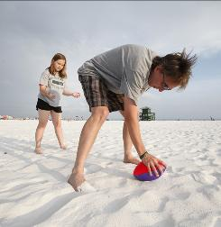 Dave Glaser and his daughter, Sarah, 10, toss a foam football around on Siesta Beach in Sarasota, Fla.